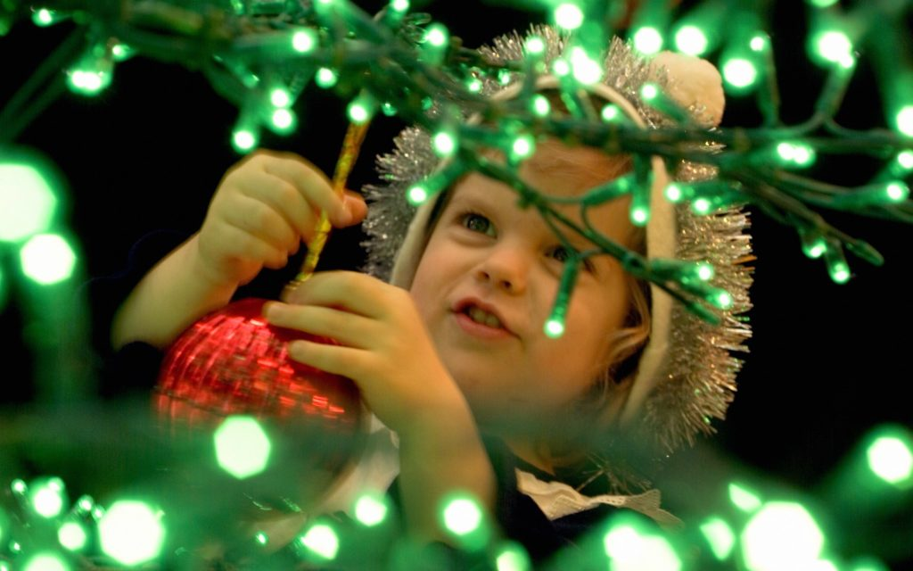 Ребенок наряжает елочку