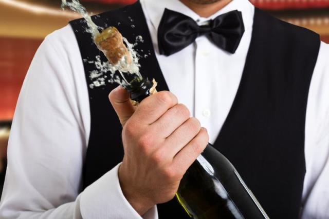 Официант открывает шампанское